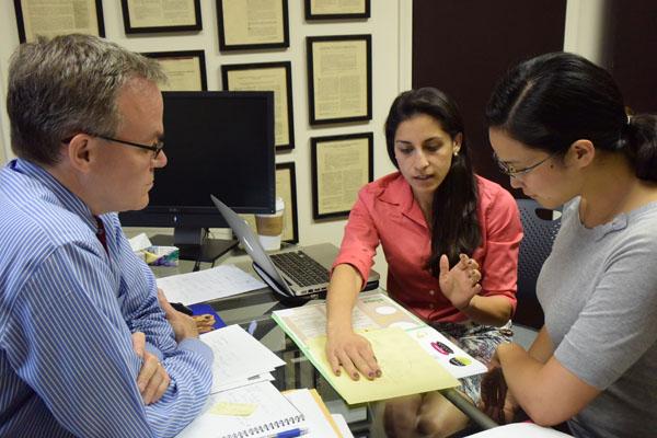 IHPI members discussing ideas around a desk