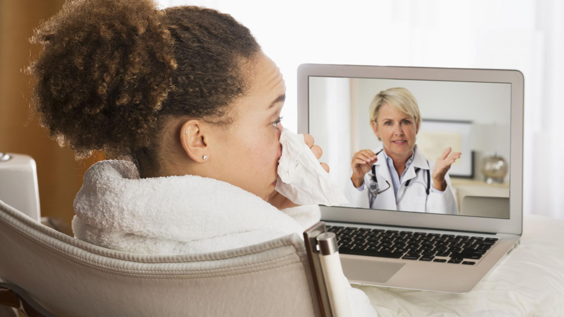 Patient with a cold having a video chat with a health provider from home